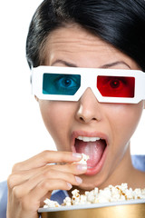 Headshot of the girl in 3D glasses eating popcorn