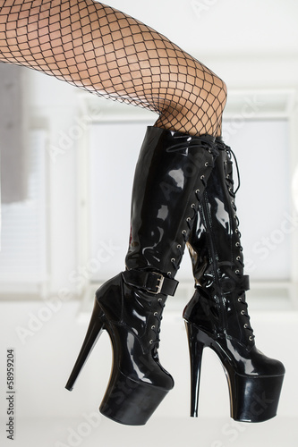 Sexy legs in fishnet stockings and black fetish boots