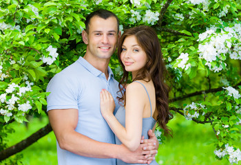 Couple embracing near blossomed tree in the park