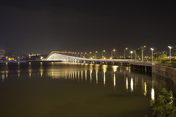 Overwater bridge over the sea at night in Macau.
