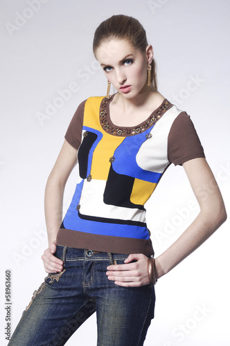 Pretty young woman in jeans with stripy shirt posing