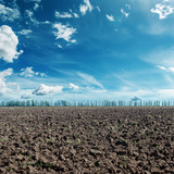 deep blue sky with clouds and black agriculture field
