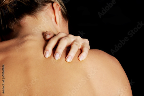 Nude, topless woman, scratching her neck.