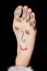 Painted funny face on the woman's feet