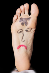 Painted sad face on the woman's feet