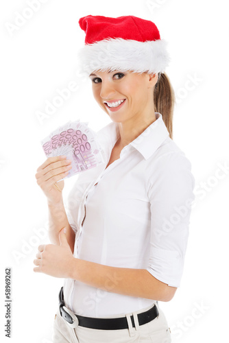 Young business woman holding money in santa hat.