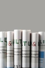 Zeitungen freigestellt vor grauem Hintergrund