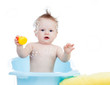baby having bath in tub and playing with soap bubble