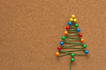 Christmas tree made of different color pins on the cork board