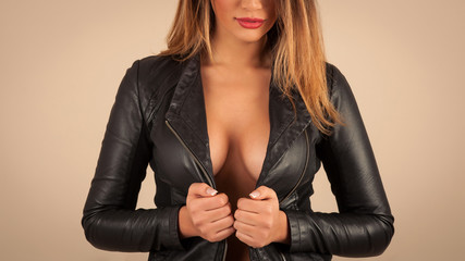 Close up of sensual nude woman wearing leather jacket.