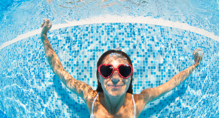 Underwater woman portrait with heart sunglasses in swimming pool
