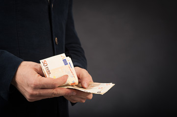 Man counting euros banknotes against black background.