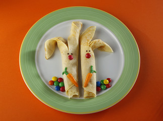 Rabbit shaped pancakes with candies on a round plate