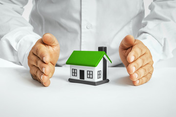 Male hands saving small house