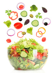 Fresh mixed vegetables falling into bowl of salad isolated