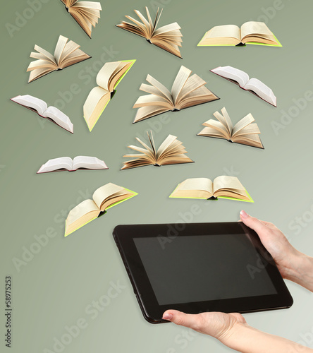 Tablet and opened books on grey background