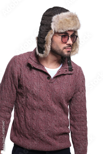 side view of a young casual man in furry hat