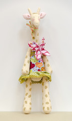 Hand made soft toy giraffe in a dress standing