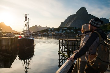 Travellers couple looking at sunset in Reine , Norway