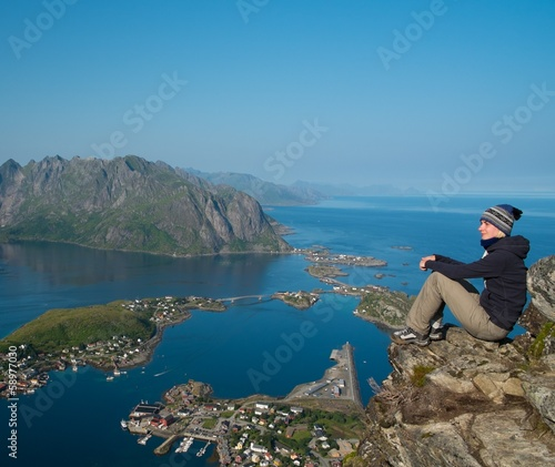 Woman hiker looking at Reine village panorama, Norway
