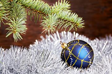Christmas decoration. Blue ball, tinsel and fir-tree