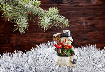 Christmas decorations. Happy snowman, fir-tree, tinsel on wooden