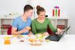 pärchen guckt beim frühstück auf laptop