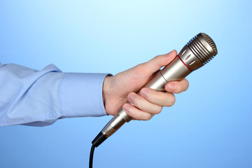 Male hand with microphone on blue background