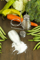 Composition of salt and pepper mills and fresh vegetables,