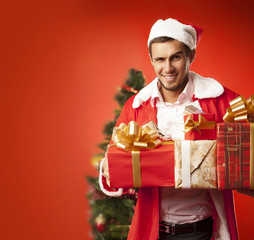 Man dressed as Santa Claus holding gifts