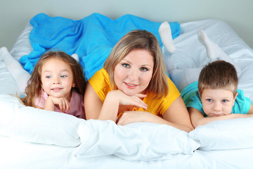 Little children with mom lying in bed