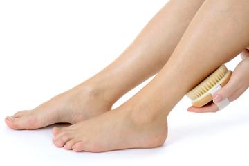 Frau massiert Beine mit Massage-Bürste