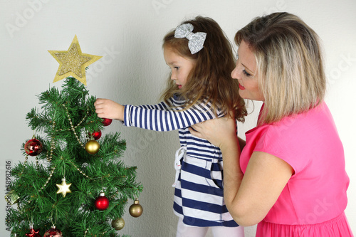 Little girl with mother decorating Christmas tree with baubles