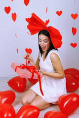 Attractive young woman with gift and balloons in room
