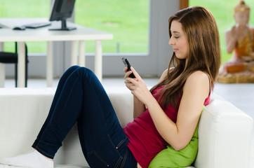 schülerin auf der couch mit smartphone