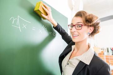 Lehrerin mit Schwamm im Klassenzimmer einer Schule
