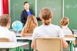 Lehrer unterrichtet an Tafel Klasse in Schule