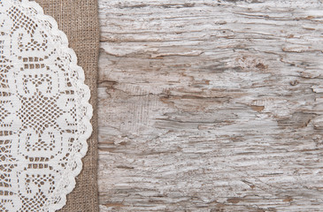 Old wood bordered by burlap and lacy cloth