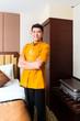 Asian Chinese porter bringing suitcase to luxury hotel room