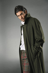 Male fashion model in green coat and tartan trousers