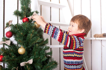 Happy kid decorating the Christmas tree with balls.