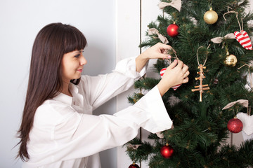 Charming woman decorating the Christmas tree with balls.