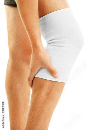 Young man with elastic bandage on knee, isolated on white