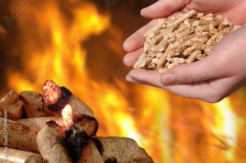 canvas print picture Hand mit brennenden Holzpellets, Feuer und Glut