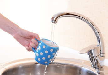 Hand holding  cup of water poured from  kitchen faucet