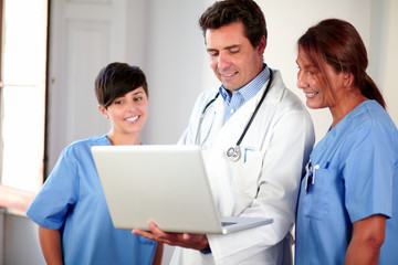 Medical group looking at laptop while standing