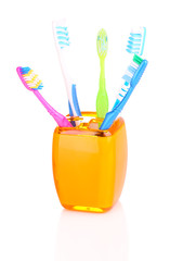 Toothbrushes in orange glass isolated on white