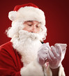 Christmas portrait of Santa Claus writing a list isolated on red