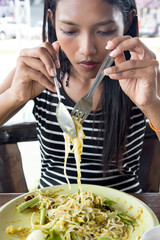 young woman eating noodles