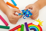 Child playing with colorful clay - closeup on hands